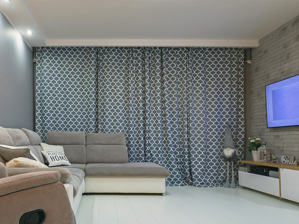 Living room grey printed curtains drawn close to block out sunlight or night light.