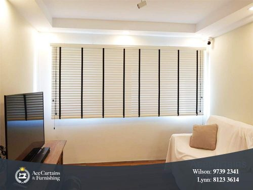 White venetian blind in a small, minimalist living room.
