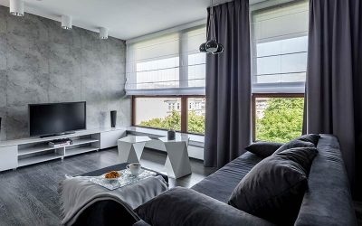 Gray dimout curtain with translucent window shades in a modern home.