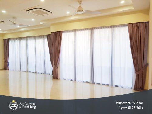 Soft white day curtains and night curtains in a bungalow's long living room.