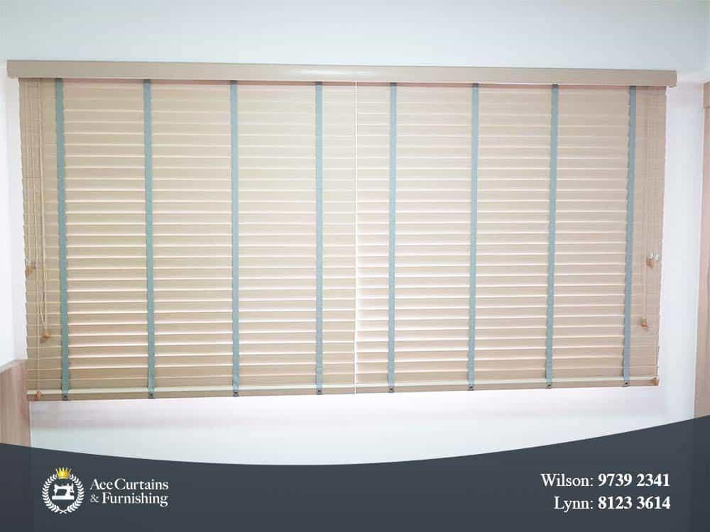 Beige PVC venetian blinds for a bedroom tilted close.