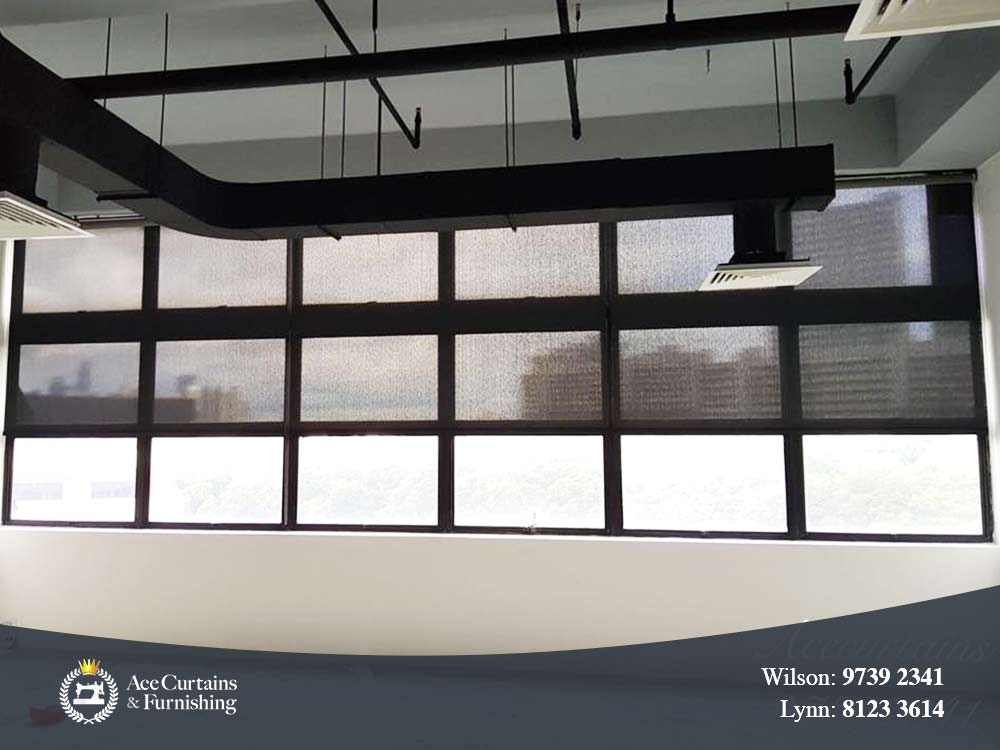 Roller blind in commercial office that acts window shade along with frosted windows.