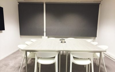Dark dimout roller blinds in a conference room keeping lights out and providing privacy.
