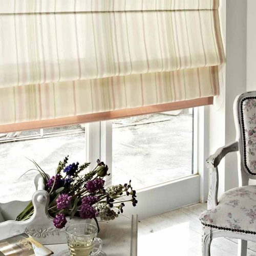 Cascading Roman blind that is letting natural light into room.