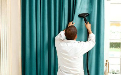 Man steam cleaning curtains to keep it clean without washing.