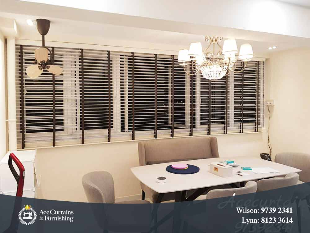 Long venetian blinds for dining room that is tilted open letting cool air in.
