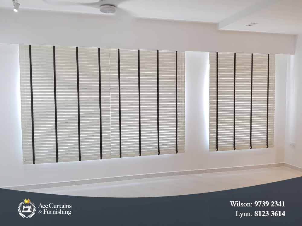 White venetian blinds tilted close in a living room.