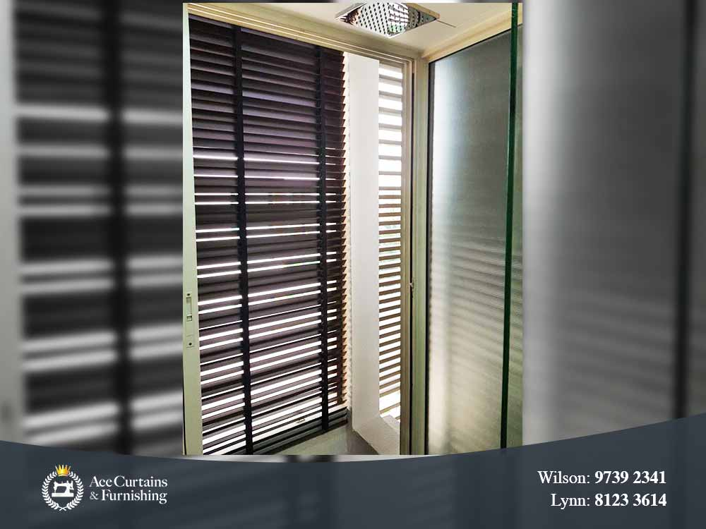 Black venetian blind that filters out light and keeps the room dark.