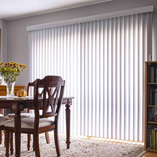 Vertical blind in a modern home filtering natural light. With dining table and bookshelf.